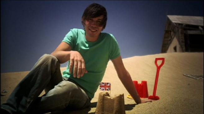 Prof Brian Cox with a sand dune