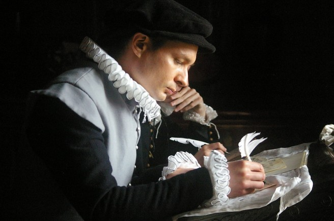 Tudor scribe writing with a quill pen on parchment