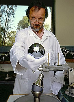 Man in a lab coat holding a sphere of silicon